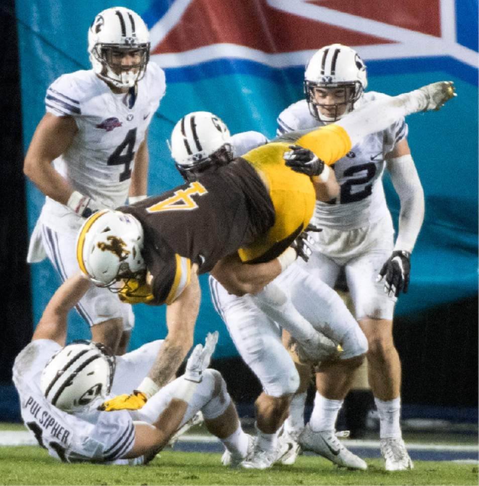 Rick Egan  |  The Salt Lake Tribune  Brigham Young Cougars linebacker Adam Pulsipher (41) pulls down Wyoming Cowboys wide receiver Tanner Gentry (4) with a little help from a team mate, as BYU defeated Wyoming 24-21in the Poinsettia Bowl, at Qualcomm Stadium in San Diego, December 21, 2016.