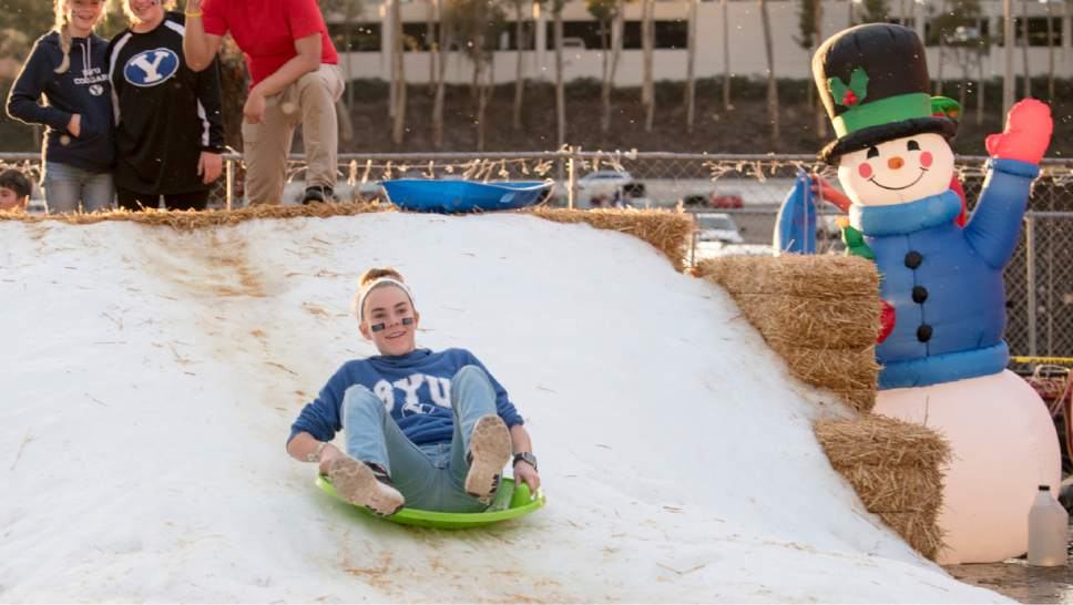 Rick Egan  |  The Salt Lake Tribune  BYU fan, Barly Barlow, 12, Camarillo, Ca   takes a ride on a sled on a pile of snow in the parking lot of Qualcomm Stadium before the Poinsettia Bowl, Brigham Young Cougars vs. Wyoming Cowboys at Qualcomm Stadium in San Diego, December 21, 2016.