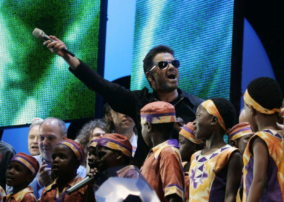 FILE - In this Saturday, July 2, 2005 file photo, British singer George Michael accompanied by other musicians and children from Africa wave to the crowds goodbye at the finale the Live 8 concert in Hyde Park, London. George Michael, who rocketed to stardom with WHAM! and went on to enjoy a long and celebrated solo career lined with controversies, has died, his publicist said on Christmas day, Sunday, Dec. 25, 2016. He was 53. (AP Photo/Lefteris Pitarakis,File)