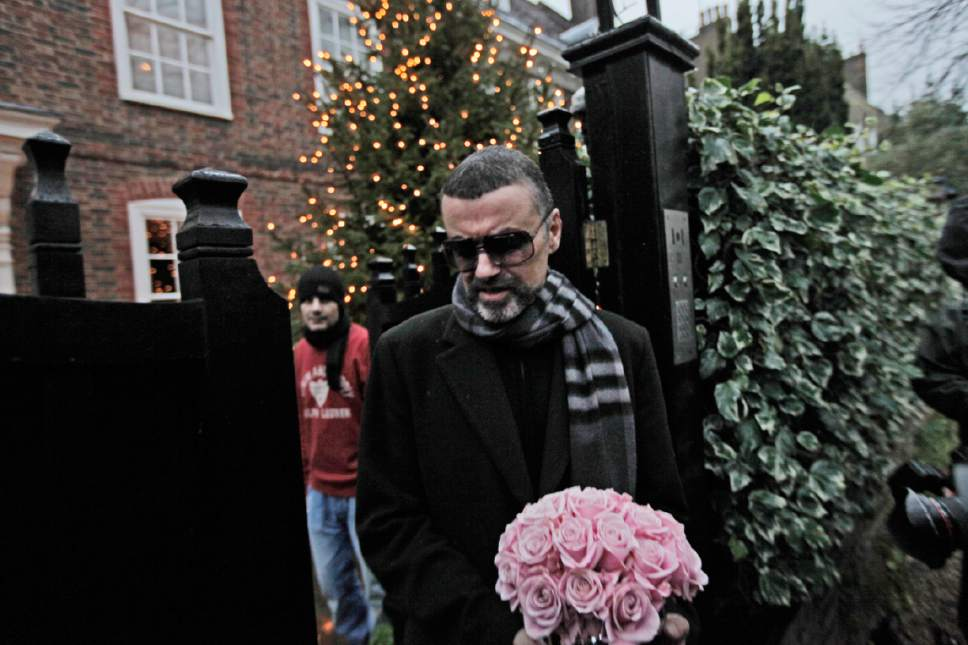 FILE - In this Friday, Dec. 23, 2011 file photo, British singer George Michael leaves his house in north London, after recovering from a life-threatening bout with pneumonia that kept him in a Vienna hospital for a month. George Michael, who rocketed to stardom with WHAM! and went on to enjoy a long and celebrated solo career lined with controversies, has died, his publicist said on Christmas day, Sunday, Dec. 25, 2016. He was 53. (AP Photo/Lefteris Pitarakis,File)