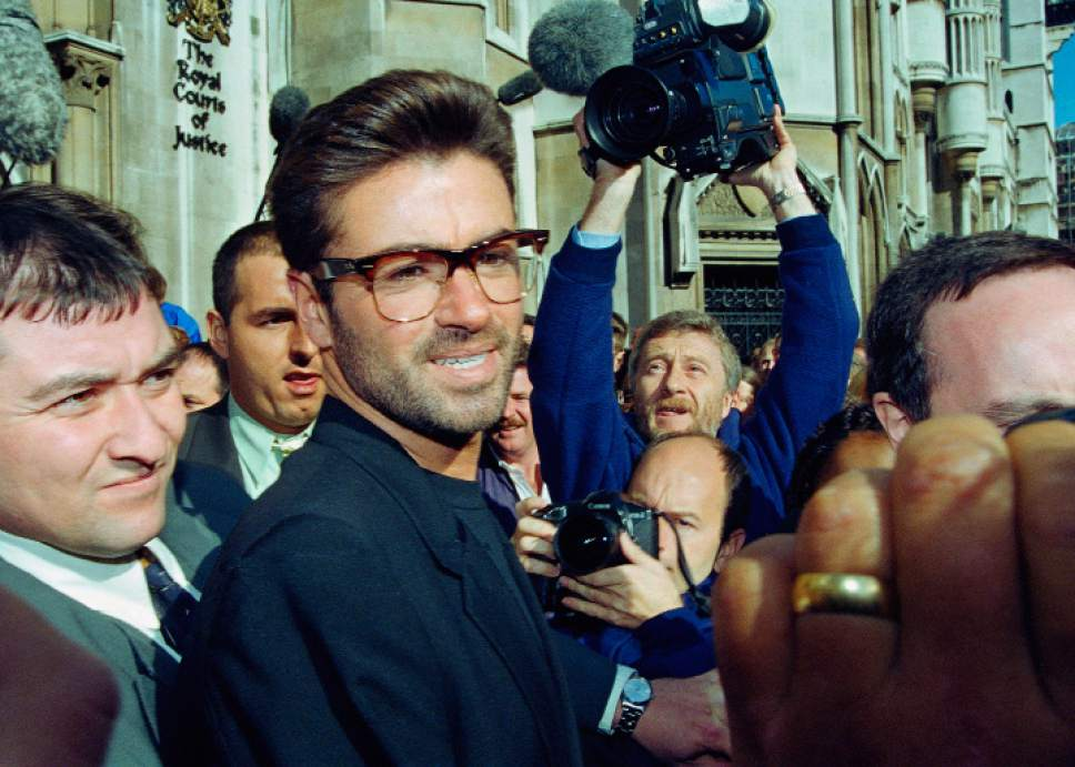 FILE - In this Monday, Oct. 18, 1993, file photo, pop star George Michael, 30, outside the Royal Courts of Justice in London at the start of his court action against Sony Music Entertainment (UK) Ltd. Michael, who rocketed to stardom with WHAM! and went on to enjoy a long and celebrated solo career lined with controversies, has died, his publicist said Sunday, Dec. 25, 2016. He was 53. (AP Photo/Alistair Grant, File)