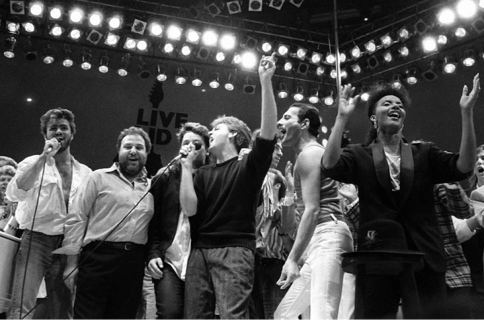 FILE - In this July 13, 1985, file photo, from left, George Michael of Wham!, concert promoter Harvey Goldsmith, Bono of U2, Paul McCartney, concert organizer Bob Geldof and Freddie Mercury of Queen join in the finale of the Live Aid famine relief concert, at Wembley Stadium, London. Michael, who rocketed to stardom with WHAM! and went on to enjoy a long and celebrated solo career lined with controversies, has died, his publicist said Sunday, Dec. 25, 2016. He was 53. (AP Photo/Joe Schaber, File)