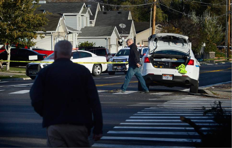 Scott Sommerdorf   |  The Salt Lake Tribune   Officers and investigators at the scene where West Valley City officer Cody Brotherson was struck and killed by a vehicle near 4100s, and 2200w in West Valley City, Sunday, November 6, 2016. Officer Brotherson's car is at right with it's trunk open. Preliminary information suggests that he may have been trying to lay tire spikes in the roadway when he was hit.