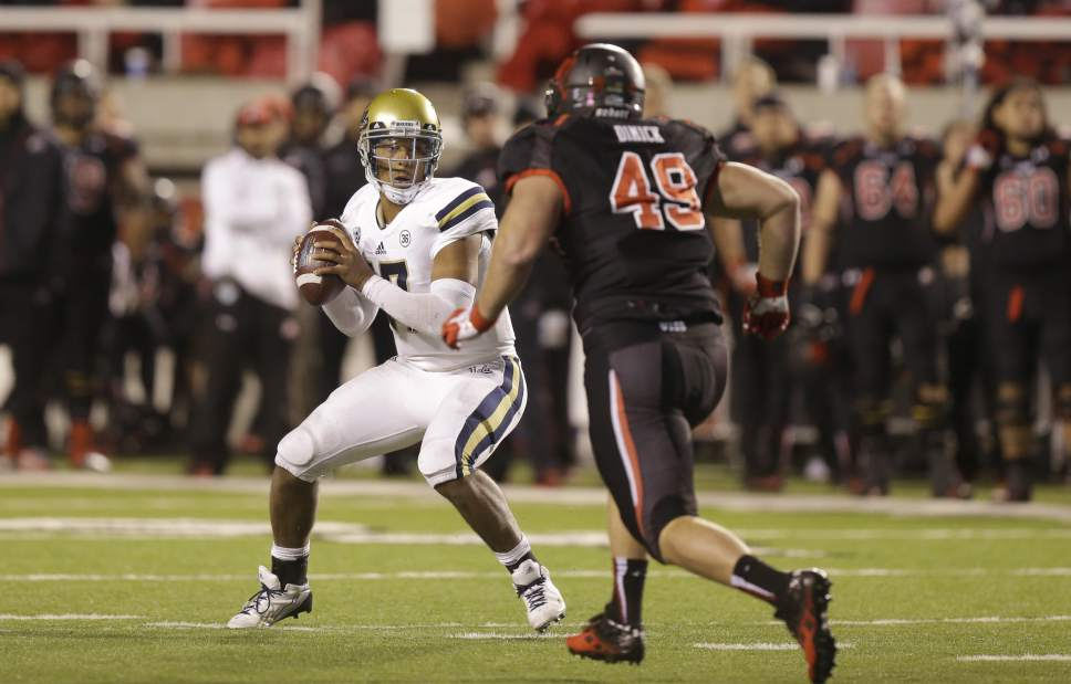 Utah defensive end Hunter Dimick (49) rushes UCLA quarterback Brett Hundley, left, in the second half during an NCAA college football game Thursday, Oct. 3, 2013, in Salt Lake City.   (AP Photo/Rick Bowmer)