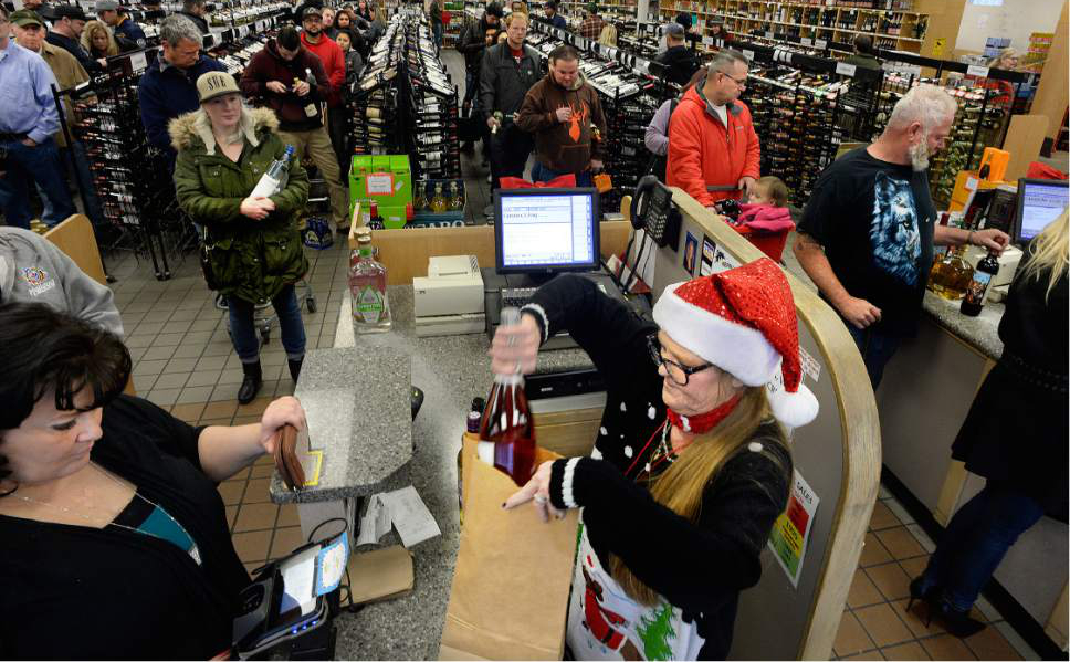 Scott Sommerdorf   |  The Salt Lake Tribune   Cashier Cayra Peterson bags up an order as some lines are 10 people deep at the State Liquor and Wine store at 125 West and 900 South in Sandy, Saturday, Dec. 24, 2016.
