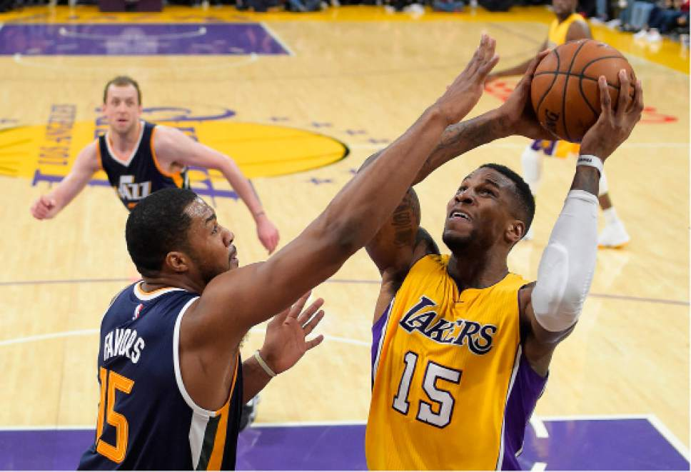 Los Angeles Lakers forward Thomas Robinson, right, shoots as Utah Jazz forward Derrick Favors defends during the second half of an NBA basketball game, Tuesday, Dec. 27, 2016, in Los Angeles. The Jazz won 102-100. (AP Photo/Mark J. Terrill)