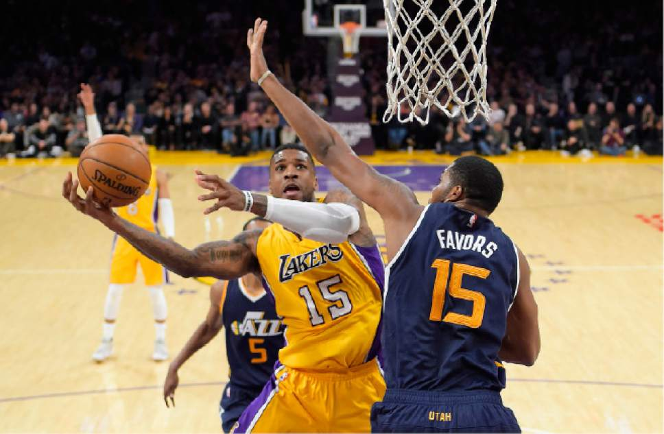 Los Angeles Lakers forward Thomas Robinson, left, shoots as Utah Jazz forward Derrick Favors defends during the second half of an NBA basketball game, Tuesday, Dec. 27, 2016, in Los Angeles. The Jazz won 102-100. (AP Photo/Mark J. Terrill)