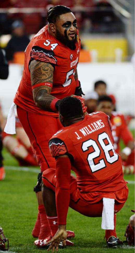 Steve Griffin / The Salt Lake Tribune  Utah Utes offensive lineman Isaac Asiata (54)helps Utah Utes running back Joe Williams (28) up after the Utes warmed up prior to the start of the Foster Farms Bowl at Levi's Stadium in Santa Clara California  Wednesday December 28, 2016.
