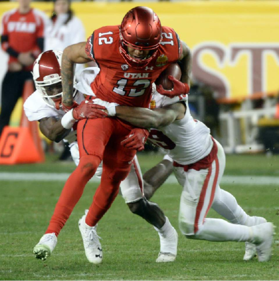 Steve Griffin / The Salt Lake Tribune  Utah Utes wide receiver Tim Patrick (12) gets wrapped up by the Indiana defense after catching a slant pass during the Foster Farms Bowl at Levi's Stadium in Santa Clara California  Wednesday December 28, 2016.