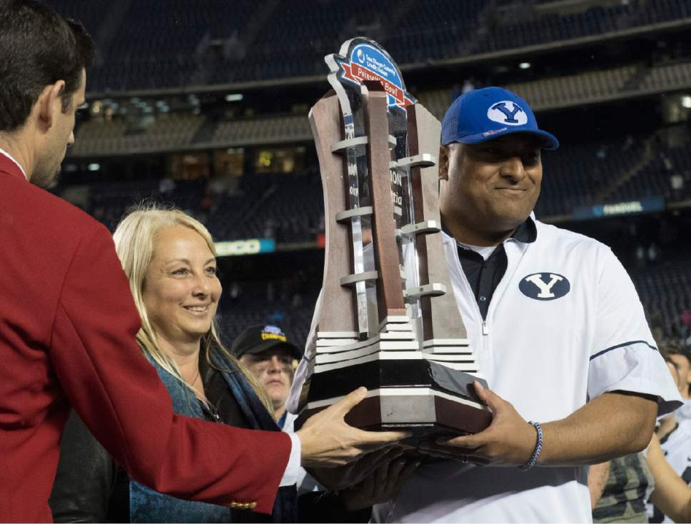 Rick Egan  |  The Salt Lake Tribune  Brigham Young Cougars head coach Kalani Sitake holds the trophy after BYU defeated Wyoming 24-21in the Poinsettia Bowl, at Qualcomm Stadium in San Diego, December 21, 2016.