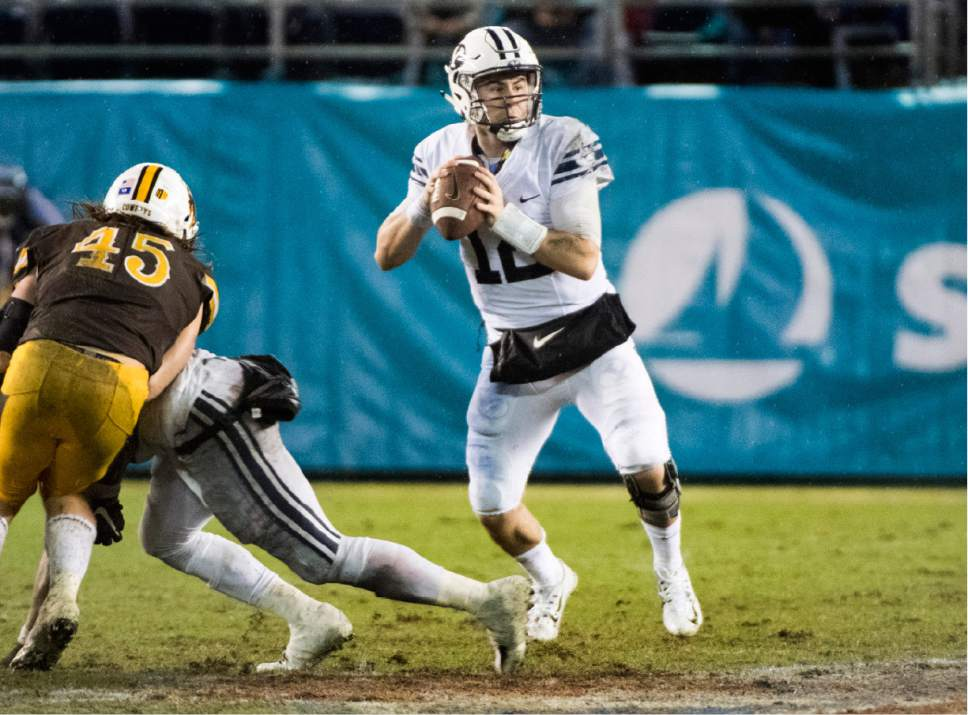 Rick Egan  |  The Salt Lake Tribune  Brigham Young Cougars quarterback Tanner Mangum (12) looks for an open man, in the Poinsettia Bowl, at Qualcomm Stadium in San Diego, December 21, 2016.
