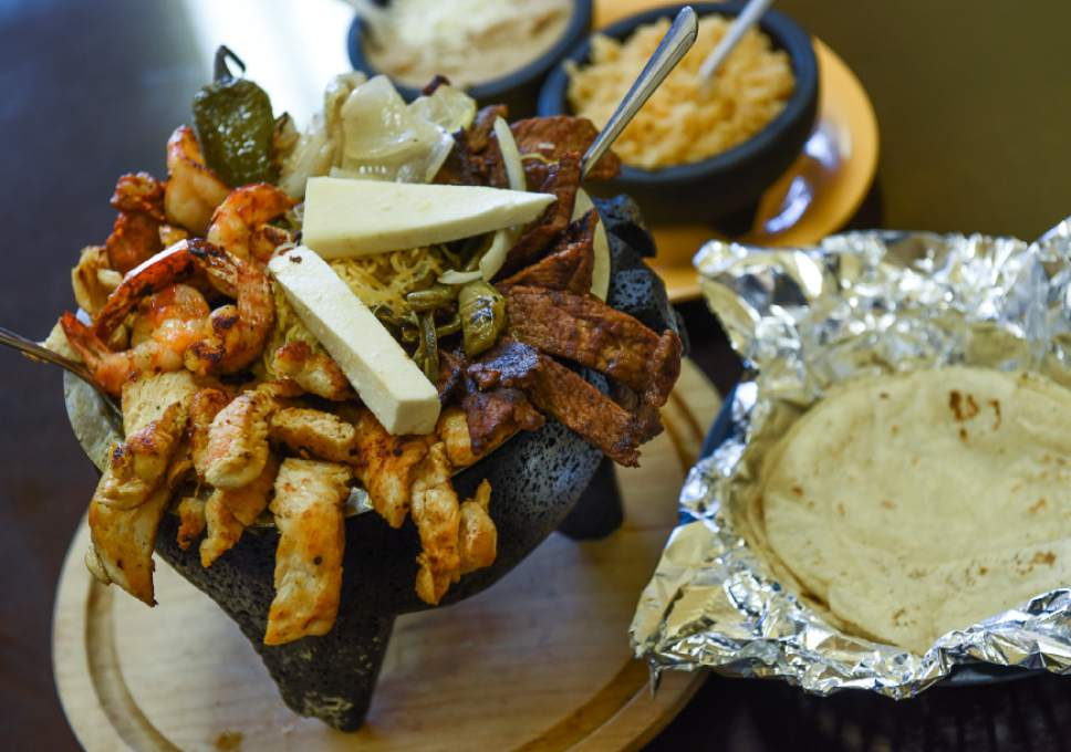 Francisco Kjolseth | The Salt Lake Tribune The family-sized Molcajete from Los Molcajetes in West Valley City. The signature dish is an overflowing lava rock filled full of a delicious green tomatillo sauce, melted cheese, chicken, steak, cactus, roasted chiles and shrimp and a side of tortillas, rice and beans.
