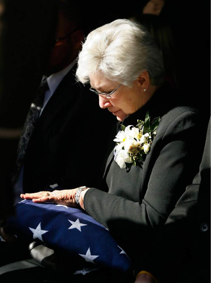 Gail Miller looks down on the American flag presented to her by the Utah Highway Patrol during the burial of her husband and Utah Jazz owner Larry H. Miller  in the Salt Lake City Cemetery in Salt Lake City, Utah, Saturday, Feb. 28, 2009.  Jeffrey D. Allred, Deseret News Pool Photo