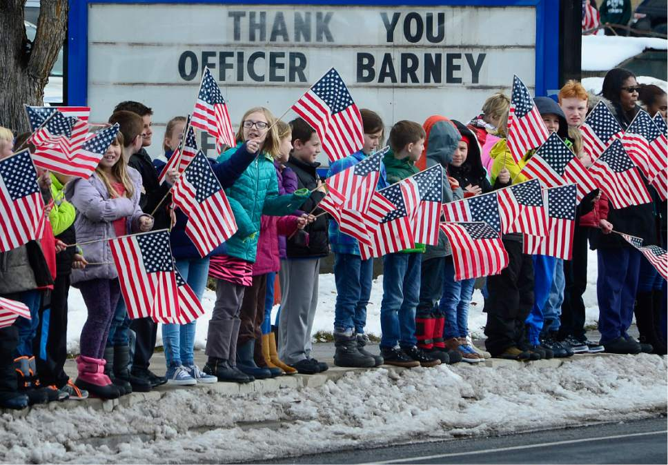Scott Sommerdorf   |  The Salt Lake Tribune Some of the 400-some students from Cottonwood Elementary show their respect for Officer Douglas Scott Barney, as about 400 of their students lined Holladay Boulevard along the funeral procession, Monday, January 25, 2016.