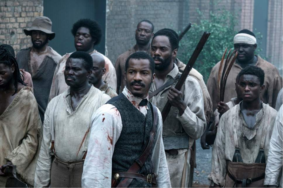 "This image released by Fox Searchlight Films shows Nate Parker as Nat Turner, center, in a scene from ""The Birth of a Nation."" (Jahi Chikwendiu/Fox Searchlight via AP)"