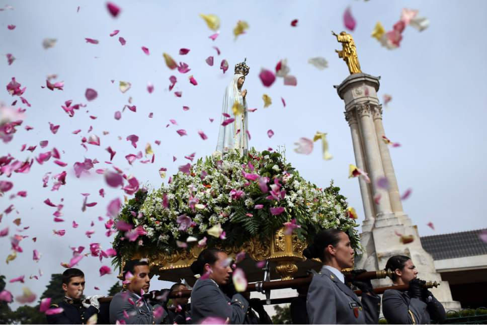 FILE - In this Wednesday, May 13, 2015 file photo, worshipper throw flower petals at the statue of the Our Lady of Fatima as it is carried at the Our Lady of Fatima shrine, in Fatima, central Portugal. The centennial of the miracle will be observed in 2017 with a visit by the pope, and it's one reason that Portugal has turned up on several lists for where to go in the new year. (AP Photo/Francisco Seco, File)