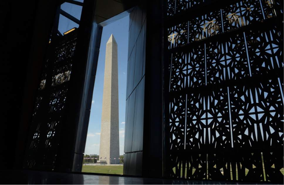 FILE - This Sept. 14, 2016 photo shows the Washington Monument framed by a window at the National Museum of African American History and Culture in Washington. The new museum is a huge draw for visitors to Washington in 2017, but all eyes will also be on the city for Donald Trump's inauguration Jan. 20 and an anti-Trump march Jan. 21. (AP Photo/Susan Walsh, File)