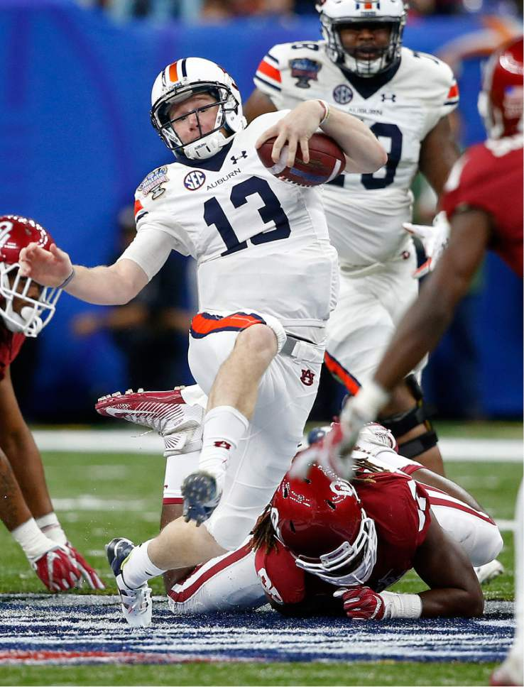 Auburn quarterback Sean White (13) is tripped up as he carries in the first half of the Sugar Bowl NCAA college football game against Oklahoma in New Orleans, Monday, Jan. 2, 2017. (AP Photo/Gerald Herbert)