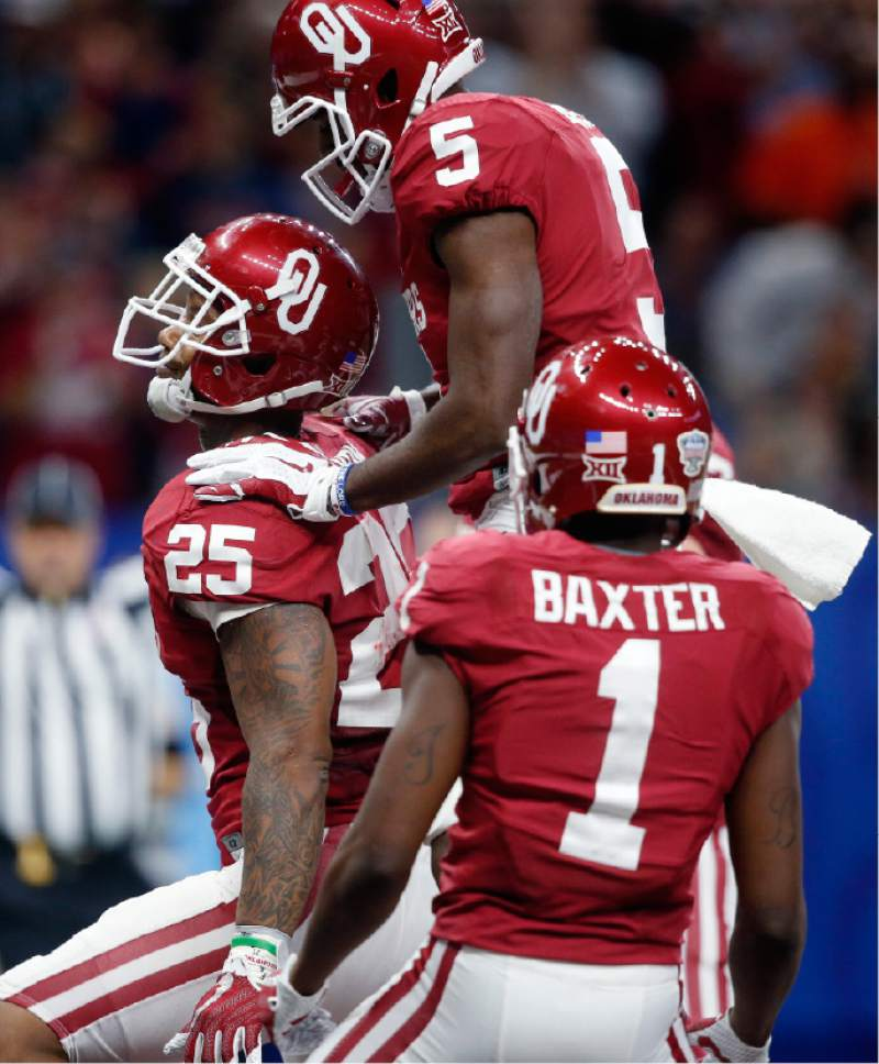Oklahoma running back Joe Mixon (25) celebrates his touchdown with wide receivers Geno Lewis (5) and Jarvis Baxter (1) in the first half of the Sugar Bowl NCAA college football game in New Orleans, Monday, Jan. 2, 2017. (AP Photo/Gerald Herbert)