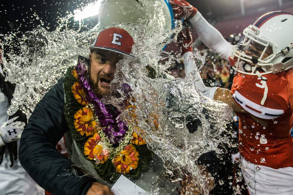 Chris Detrick  |  The Salt Lake Tribune East's Lachlan Zuchetto (13) and East's Julian Chavez (3) pour a cooler of ice water on head coach Brandon Matich after winning the 4A football championship at Rice-Eccles Stadium Friday November 18, 2016. East defeated Springville 48-20.