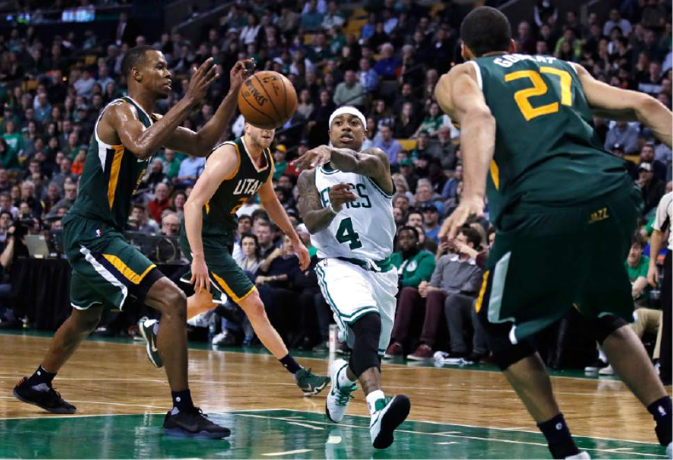 Boston Celtics guard Isaiah Thomas (4) passes the ball as he drives between the Utah Jazz during the second half of an NBA basketball game in Boston, Tuesday, Jan. 3, 2017. Thomas had 29 points and 15 assists as the Celtics defeated the Jazz 115-104. (AP Photo/Charles Krupa)
