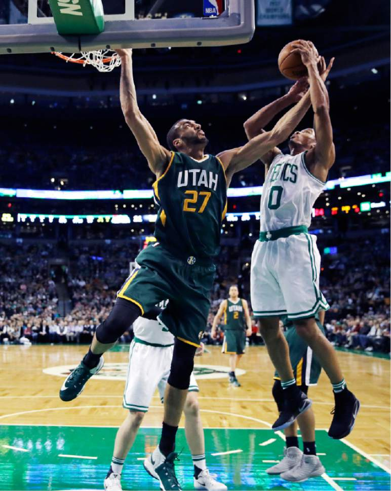 Utah Jazz center Rudy Gobert (27) and Boston Celtics guard Avery Bradley (0) leap for a rebound during the first quarter of an NBA basketball game in Boston, Tuesday, Jan. 3, 2017. (AP Photo/Charles Krupa)