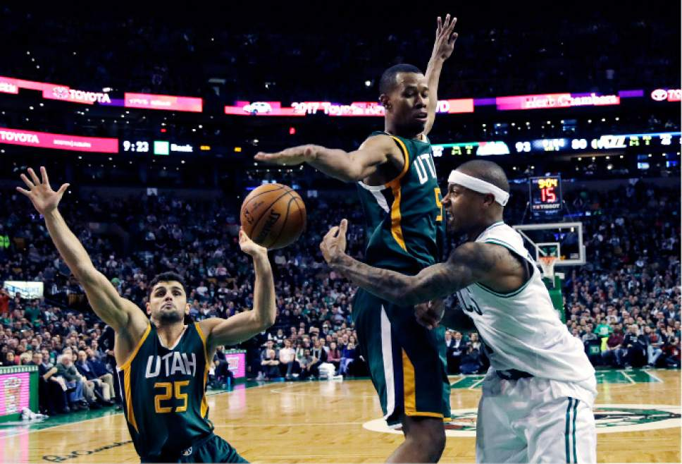 Boston Celtics guard Isaiah Thomas, right, passes the ball as he is pressured by Utah Jazz guards Rodney Hood, center, and Raul Neto (25), of Brazil, during the second half of an NBA basketball game in Boston, Tuesday, Jan. 3, 2017. Thomas had 29 points and 15 assists as the Celtics defeated the Jazz 115-104. (AP Photo/Charles Krupa)