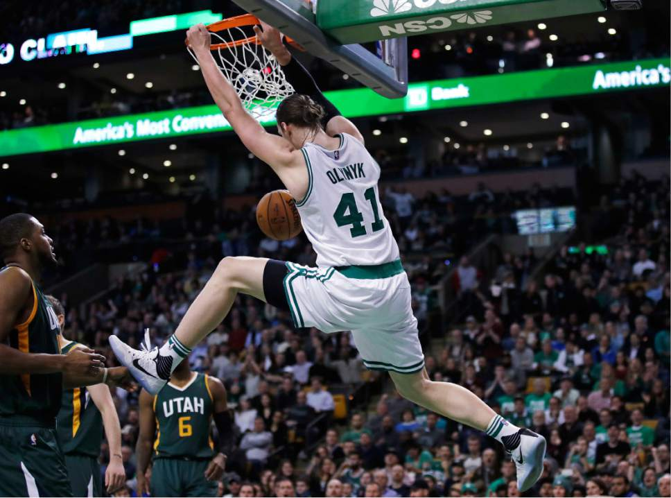 Boston Celtics center Kelly Olynyk (41) hangs on the rim on a dunk during the second half of an NBA basketball game against the Utah Jazz in Boston, Tuesday, Jan. 3, 2017. The Celtics defeated the Jazz 115-104. (AP Photo/Charles Krupa)