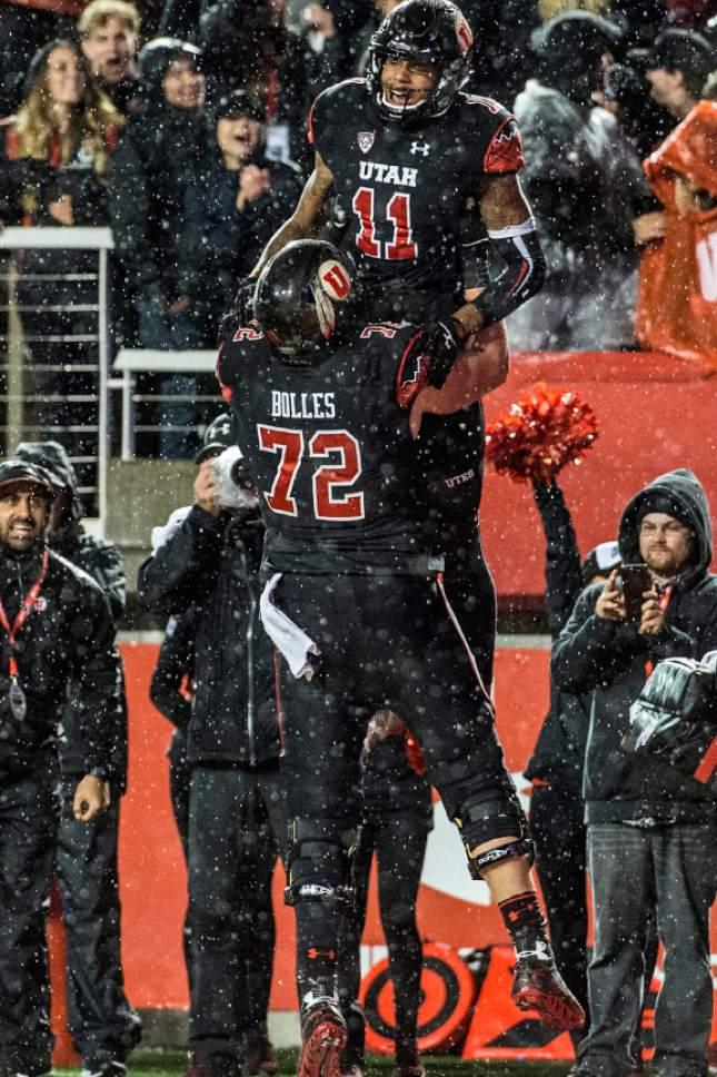 Chris Detrick  |  The Salt Lake Tribune Utah Utes offensive lineman Garett Bolles (72) picks up Utah Utes wide receiver Raelon Singleton (11) after Singleton scored a touchdown during the game at Rice-Eccles Stadium Friday September 23, 2016. Utah Utes defeated USC Trojans 31-27.
