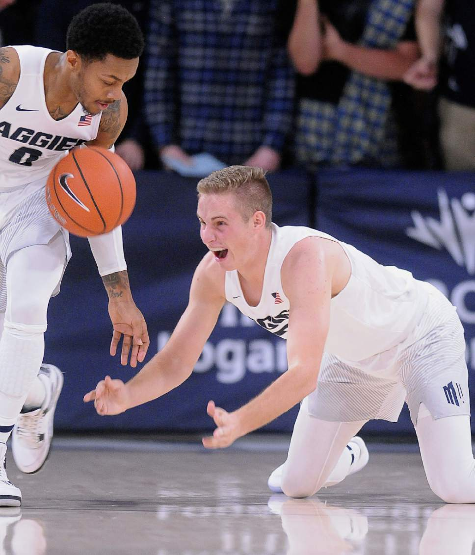 Utah State guard Sam Merrill (3) tosses the ball to guard Shane Rector (0) after stealing it from New Jersey Institute guard Damon Lynn during an NCAA college basketball game Monday, Nov. 14, 2016, in Logan, Utah. (Eli Lucero/The Herald Journal via AP)