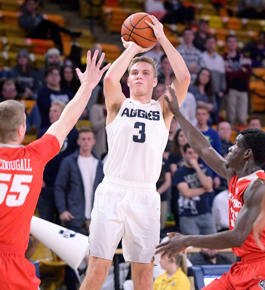 Utah State guard Sam Merrill (3) takes a shot as New Mexico forward Connor MacDougall (55) and guard Damien Jefferson (24) defend Wednesday, Jan. 4, 2017, in Logan, Utah. (Eli Lucero/The Herald Journal via AP)