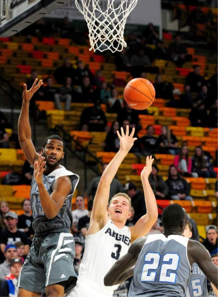 Utah State's Sam Merrill puts up a shot around University of New Orlean's Jorge Rosa during an NCAA college basketball game, Monday, Dec. 19, 2016, in Logan, Utah. (John Zsiray/Herald Journal via AP)