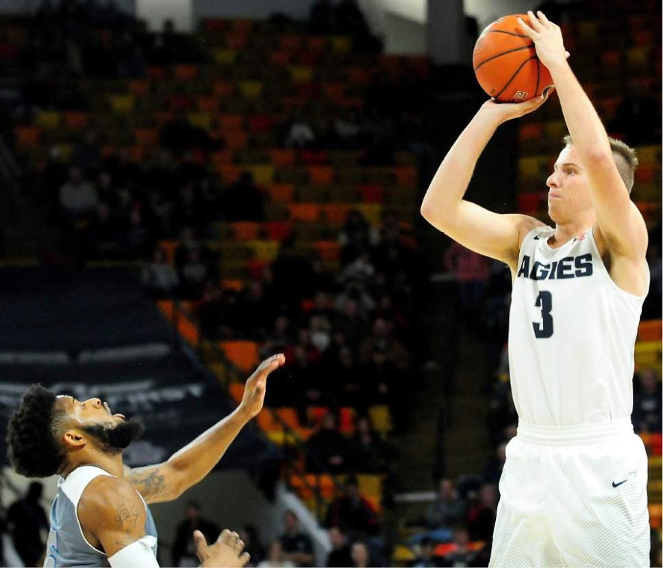 Utah State's Sam Merrill puts up a shot over University of New Orleans' Travin Thibodeaux during an NCAA college basketball game, Monday, Dec. 19, 2016, in Logan, Utah. (John Zsiray/Herald Journal via AP)