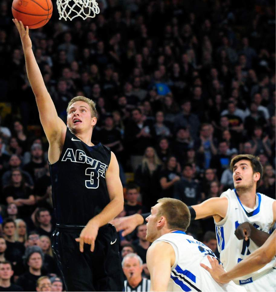 Utah State's Sam Merrill goes up for a layup in front of two Indiana State players during an NCAA college basketball game Saturday, Dec. 3, 2016, in Logan, Utah. (John Zsiray/Herald Journal via AP) /The Herald Journal via AP)