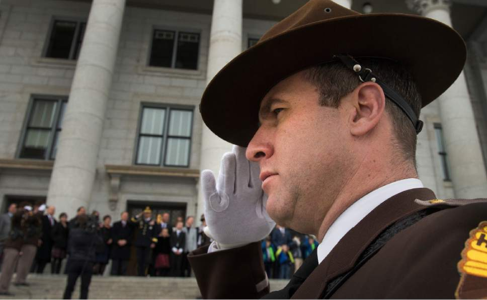 Leah Hogsten  |  The Salt Lake Tribune Utah Highway Patrol Trooper Lawrence Hopper salutes as three howitzers fire in a 19-gun salute and helicopters fly over the Utah National Guard at the conclusion of the 2017 State Inaugural Ceremony for Gov. Gary R. Herbert, January 4, 2017 at the Utah State Capitol.