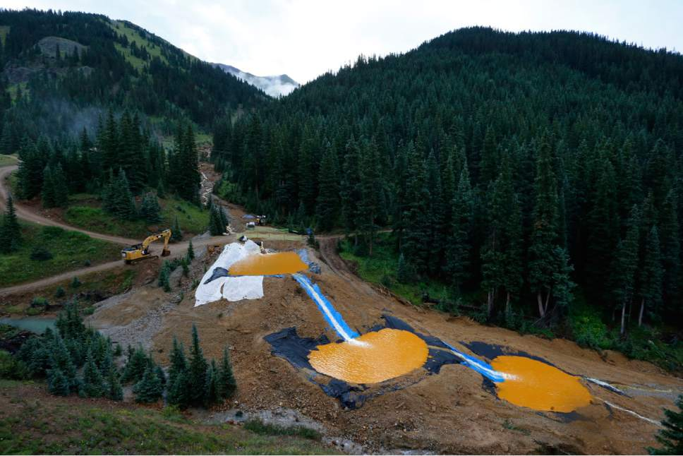 FILE - In this Aug. 12, 2015 file photo, water flows through a series of retention ponds built to contain and filter out heavy metals and chemicals from the Gold King mine chemical accident, in the spillway about 1/4 mile downstream from the mine, outside Silverton, Colo. The massive mine waste spill in southwestern Colorado contributed to water quality problems for up to nine months, the Environmental Protection Agency said Friday, Jan. 6, 2017. Contamination from the August 2015 spill at the Gold King Mine may also have caused pollution problems last year when annual spring snowmelt swelled rivers. (AP Photo/Brennan Linsley, file)