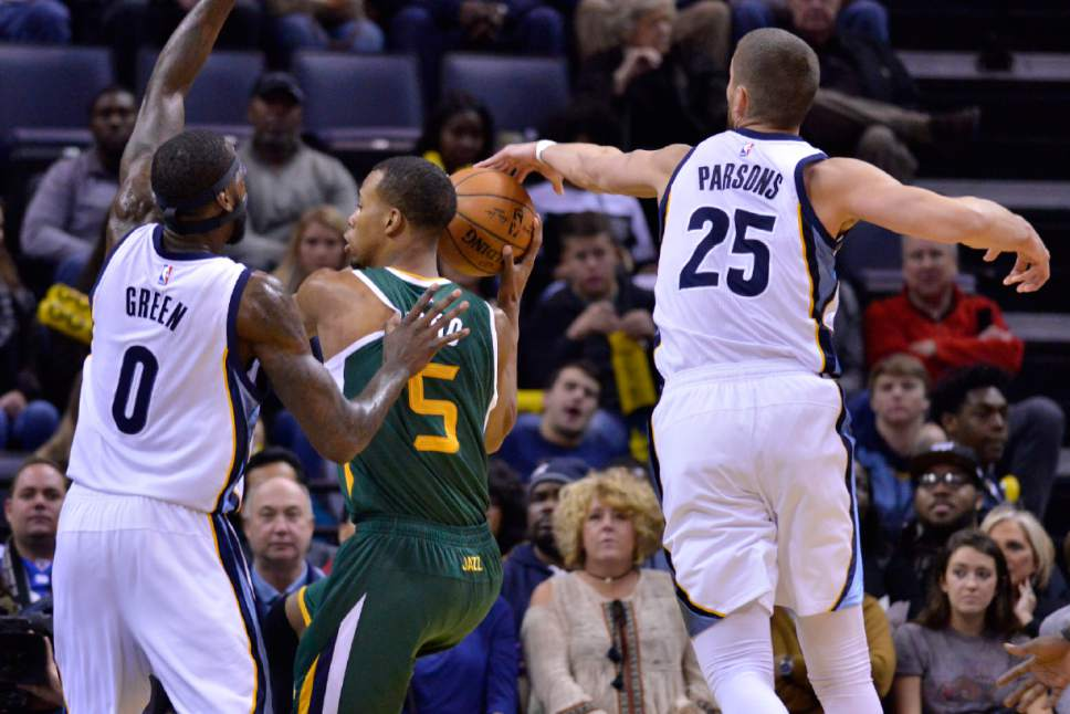 Utah Jazz guard Rodney Hood (5) controls the ball against Memphis Grizzlies forwards JaMychal Green (0) and Chandler Parsons (25) in the first half of an NBA basketball game Sunday, Jan. 8, 2017, in Memphis, Tenn. (AP Photo/Brandon Dill)