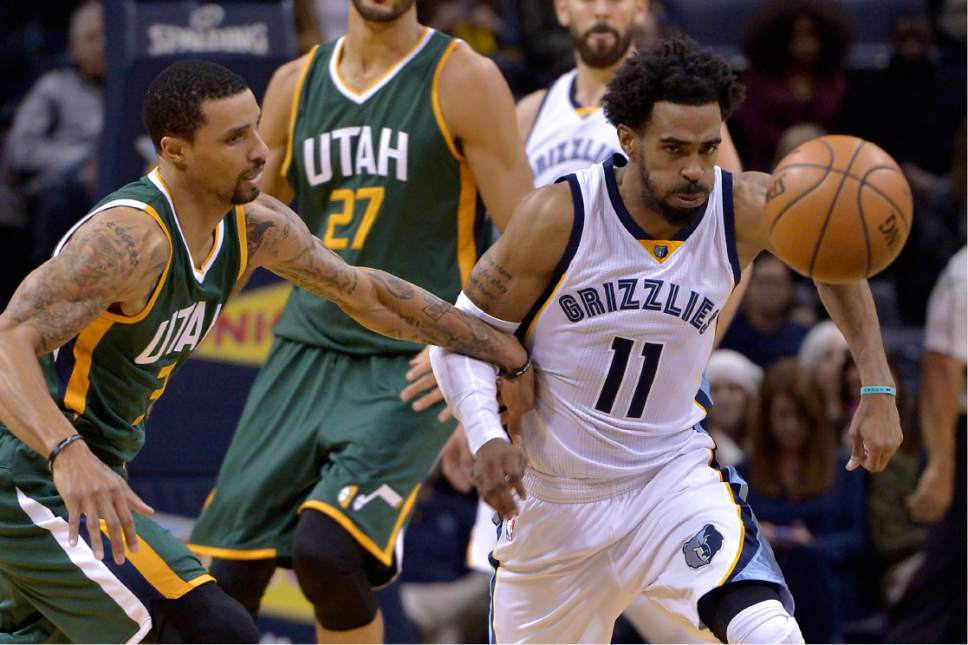 Memphis Grizzlies guard Mike Conley (11) and Utah Jazz guard George Hill (3) chase a loose ball in the first half of an NBA basketball game Sunday, Jan. 8, 2017, in Memphis, Tenn. (AP Photo/Brandon Dill)