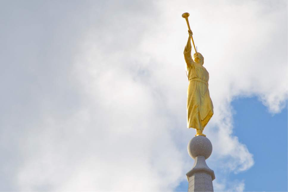 This Aug. 3, 2016 photo shows a 21-foot statue of the trumpeting Angel Moroni sits atop the new Mormon Temple, center, set to open near Logan Square in Center City in Philadelphia. The Mormon church is offering the general public a rare opportunity to tour its 152nd temple, a first of its kind in Pennsylvania.  Regional membership in The Church of Jesus Christ of Latter-day Saints has grown to more than 40,000 members in parts of Pennsylvania, Delaware, New Jersey and Maryland. The growth prompted church leadership in 2008 to announce the temple plans.  (AP Photo/Michael Sisak)