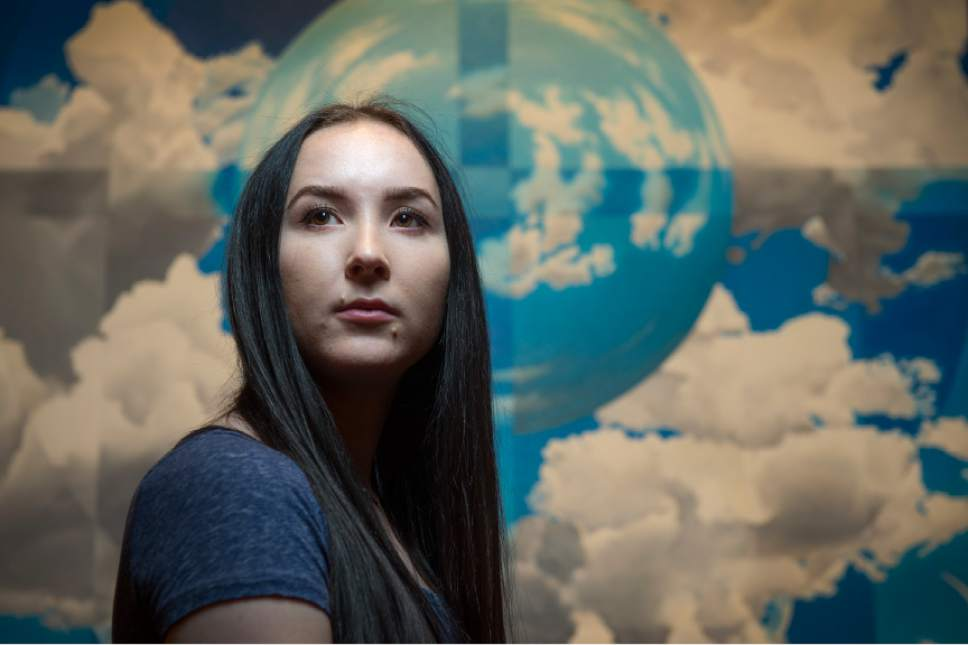 """Leah Hogsten     The Salt Lake Tribune The Salt Lake Tribune's Utahn of the Year--Madi Barney, pictured Wednesday, December 22, 2016, in front of an oil painting by Utahn Lee Cowan entitled """"Heed the Firmament to the Eighth"""", 2014, part of the collection at the Springville Art Museum. Through Barney's willingness to go public about Brigham Young University's handling of her rape case, she changed the discussion on campus sexual assault across the state. Barney launched a petition requesting Honor Code amnesty for BYU students who report sex crimes that resulted in the school's policy change not to punish sexual assault victims for Honor Code violations in connection with their reports."""