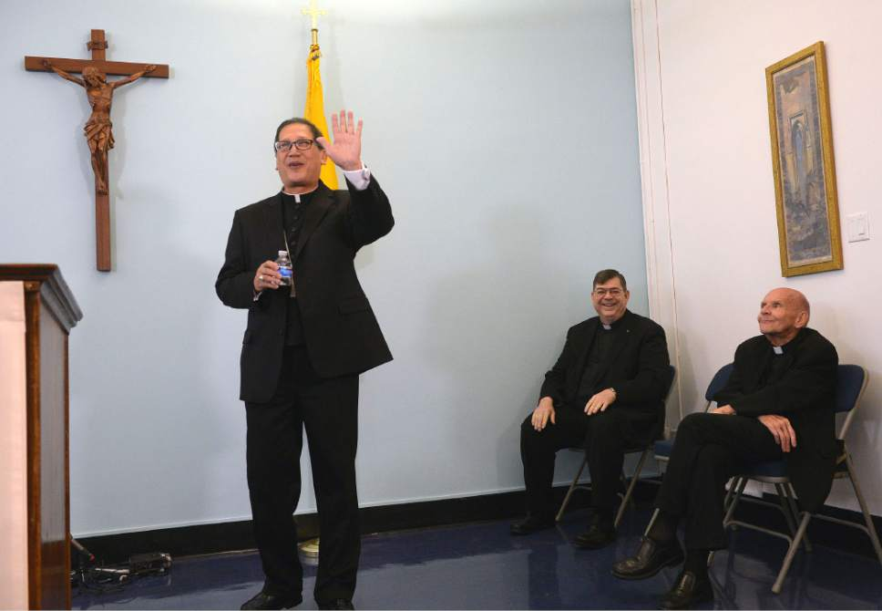 Al Hartmann  |  The Salt Lake Tribune  Bishop elect Oscar Azarcon Solis, left, waves as he's introduced as the 10th Bishop of the Catholic Diocese of Salt Lake City Tuesday Jan. 10.  Msgr. Colin Bircumshaw and Msgr. Terrence Fitzgerald at right.