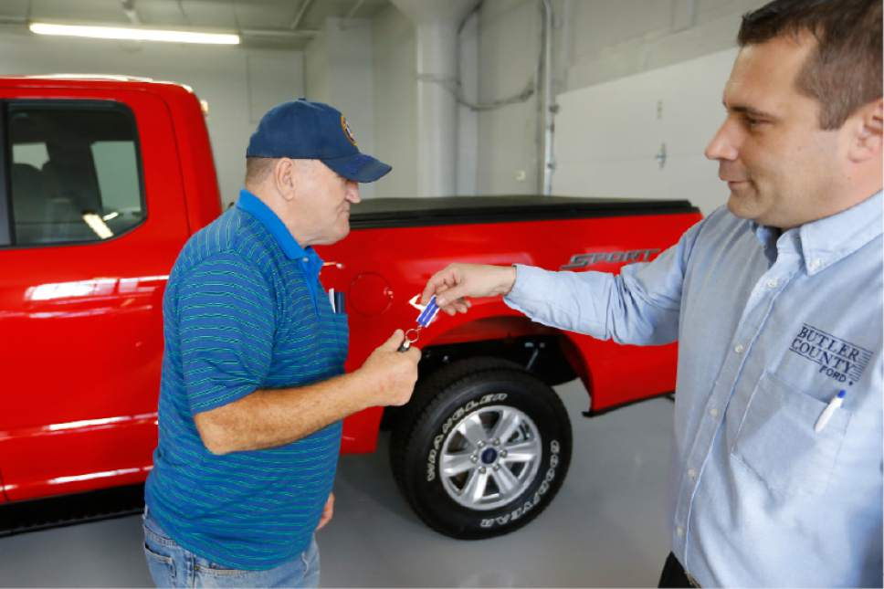 FILE - In this Thursday, Nov. 19, 2015, file photo, Alton John, left, from Kittanning, Pa., gets the keys to his new 2015 Ford F-150 Supercab 4x4 pickup truck from salesman Robert Myers as he takes delivery at Butler County Ford in Butler, Pa. U.S. car shoppers will find plentiful deals, relatively low interest rates and lots of high-tech choices in the market in 2017. (AP Photo/Keith Srakocic, File)