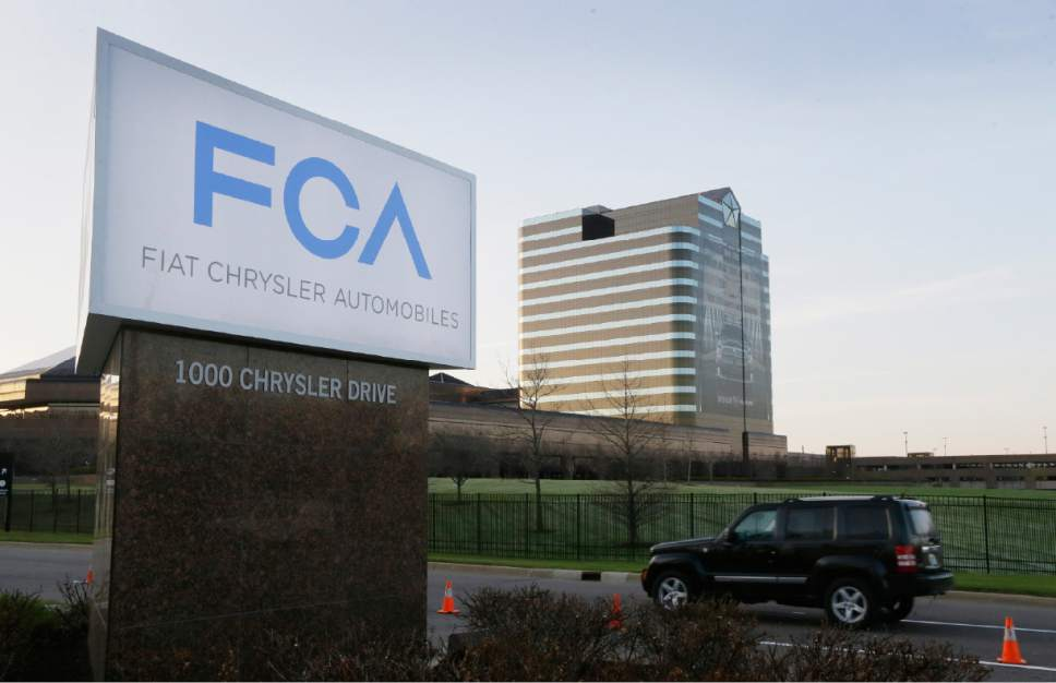 """FILE - In this Tuesday, May 6, 2014, file photo, a vehicle moves past a sign outside Fiat Chrysler Automobiles world headquarters in Auburn Hills, Mich. On Thursday, Jan. 12, 2017, the U.S. government alleged that Fiat Chrysler Automobiles failed to disclose that software in some of its pickups and SUVs with diesel engines allows them to emit more pollution than allowed under the Clean Air Act. The Environmental Protection Agency said in a statement that it issued a """"notice of violation"""" to the company that covers about 104,000 vehicles, including the 2014 through 2016 Jeep Grand Cherokee and Dodge Ram pickups, all with 3-liter diesel engines. (AP Photo/Carlos Osorio, File)"""