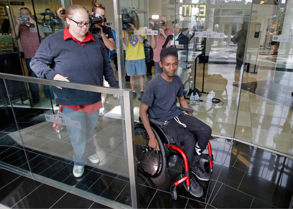 "CORRECTS SPELLING TO ABDULLAHI, NOT ABUDULLAHI - Abdullahi ""Abdi"" Mohamed, a teenage Somali refugee who was critically wounded by police during a fight outside a homeless shelter, leaves following his first court appearance on robbery and drug charges Wednesday, Aug. 10, 2016, in Salt Lake City. Salt Lake County District Attorney Sim Gill said officers acted appropriately when they fired at Mohamed because police believed he was about to seriously injure or kill a man with a metal broom handle. (AP Photo/Rick Bowmer)"