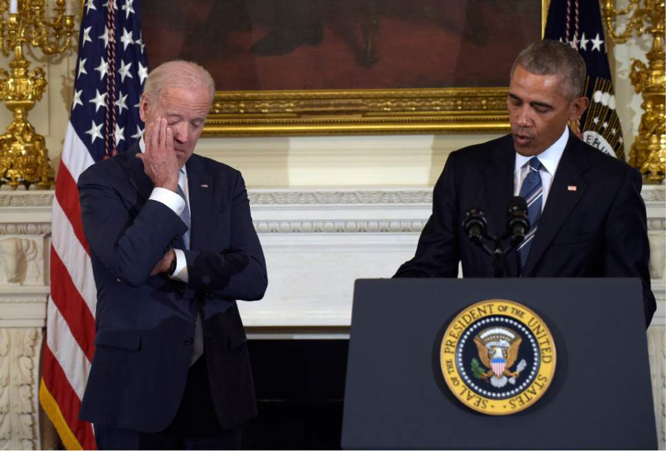 President Barack Obama, right, honors Vice President Joe Biden, left, during a ceremony in the State Dining Room of the White House in Washington, Thursday, Jan. 12, 2017. Obama surprised Biden and presented him with the Presidential Medal of Freedom. (AP Photo/Susan Walsh)