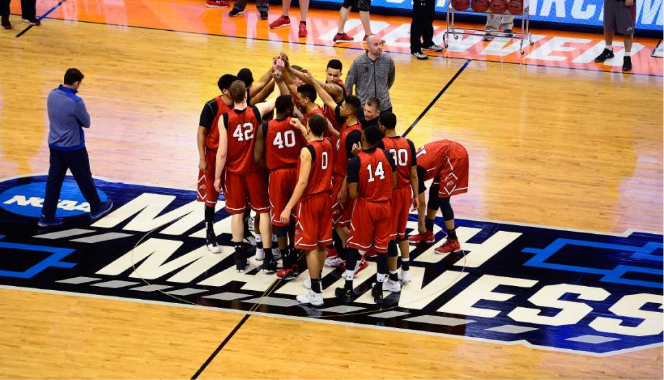 Scott Sommerdorf   |  The Salt Lake Tribune   University of Utah players gather on top of the March Madness logo at center court prior to their practice session in Denver, Wednesday, March 16, 2016.