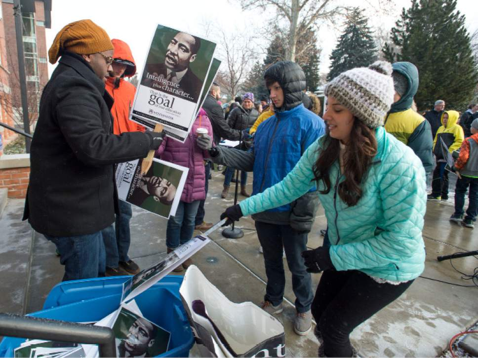 Steve Griffin / The Salt Lake Tribune  Karnell Black, left, Assistant Dean of Students at Westminster College, helps marchers with signs during a celebration of Martin Luther King Jr. Day in Salt Lake City Monday, Jan. 16, 2017. The morning event included a rally and march through Sugar House as part of the school's week-long celebration.