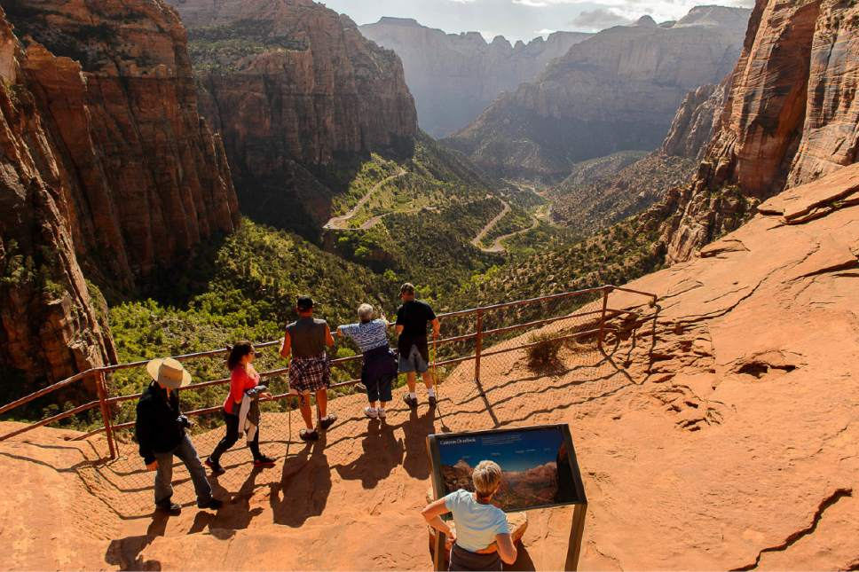 File - This May 5, 2015, file photo, shows hikers on the Canyon Overlook Trail in Zion National Park. Visits to U.S. national parks set a record in 2016 for the third consecutive year as landmarks such Zion, Yellowstone and Rocky Mountain experienced historic levels of popularity that brought collateral headaches stemming from overcrowded roads and trails and increasing visitor misbehavior. (Trent Nelson/The Salt Lake Tribune via AP, File)