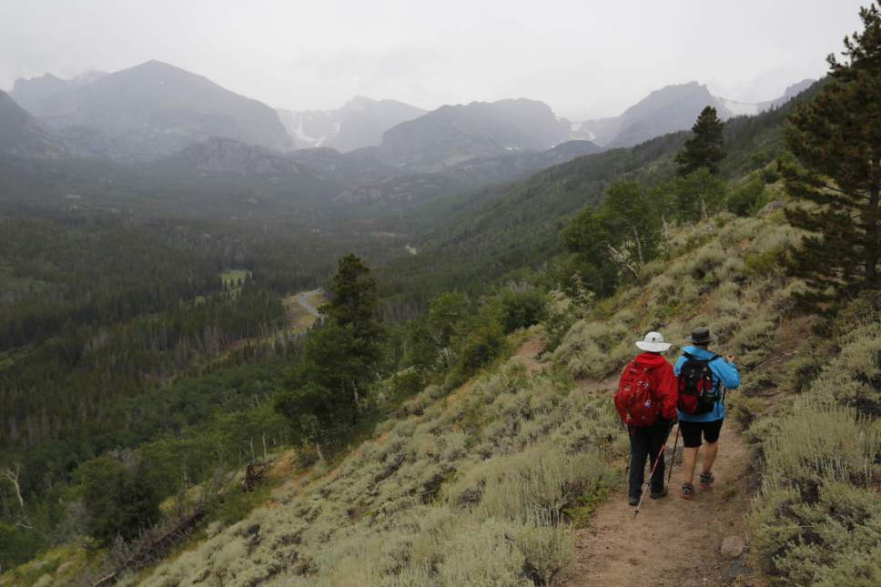 FILE - In this Aug. 4, 2016 file photo, hikers descend a ridge inside Rocky Mountain National Park, near Estes Park, Colo. Visitation to America's national parks set a record in 2016 for the third consecutive year. (AP Photo/Brennan Linsley, file)