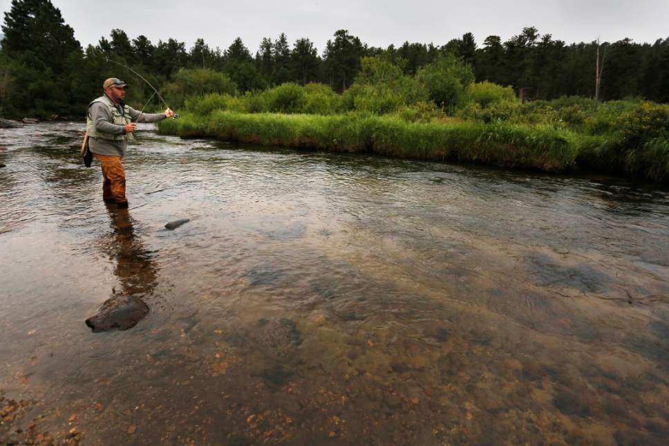 FILE - In this Aug. 4, 2016 file photo, an angler fly fishes on a pristine meandering stream inside Rocky Mountain National Park, near Estes Park, Colo. Visitation to America's national parks set a record in 2016 for the third consecutive year. (AP Photo/Brennan Linsley, file)